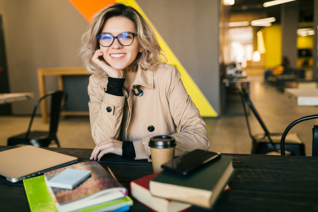 portrait-young-pretty-woman-sitting-table-trench-coat-working-laptop-co-working-office-wearing-glasses-smiling-happy-positive-workplace_285396-57